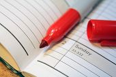 stock photo of sharpie  - Open calendar with red felt tip marker in spine - JPG
