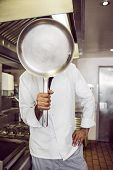 Male cook holding pan in front of his face in the kitchen