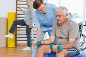 Female therapist assisting senior man with dumbbells in the medical office
