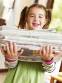 foto of recycled paper  - girl carrying newspapers for recycling looking at camera - JPG