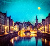 Vintage retro hipster style travel image of European medieval night city view background - Bruges (B