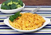 picture of oval  - Oval bowl of spiiral baked macaroni and cheese with a side dish of broccoli - JPG