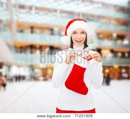 christmas, winter, happiness, holidays and people concept - smiling woman in santa helper hat with small gift box and stocking over shopping center background
