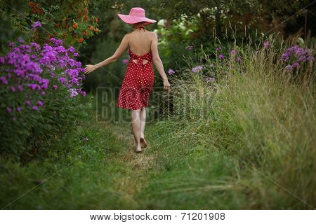 Woman In A Hat Walks Among The Flowers