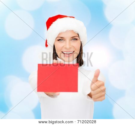 christmas, holdays, people, advertisement and sale concept - happy woman in santa helper hat with blank red card showing thumbs up gesture over blue lights background