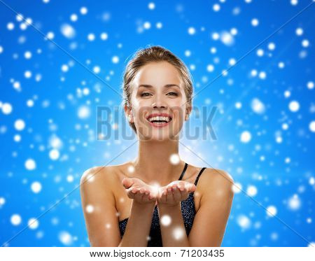 advertisement, winter holidays, christmas, people and luxury concept - laughing woman in evening dress holding something imaginary over black background over blue snowy background
