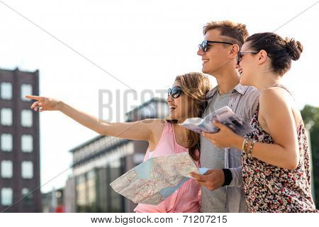 travel, tourism, vacation, summer and people concept - smiling friends with map and city guide pointing finger outdoors