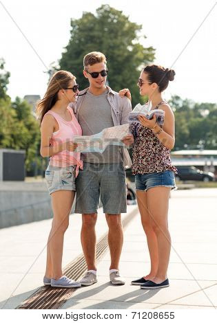 travel, tourism, vacation, summer and people concept - smiling friends with map and city guide outdoors