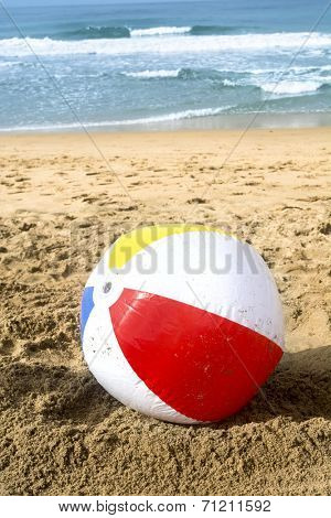 A colorful, summertime beach ball washes up to the sandy beach while a turquoise ocean rumbles peacefully in the background.