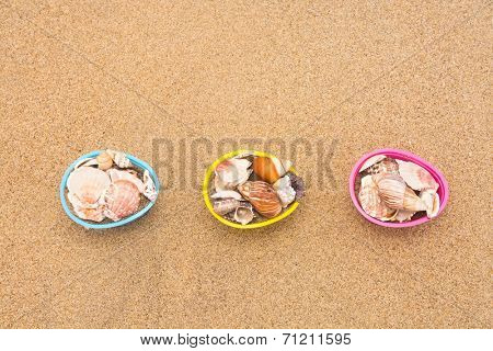 Decorative Easter egg baskets on the beach filled with seashells for use as a background. Room for copy left along the top half of the image.