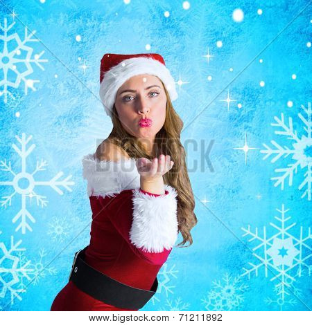 Sexy santa girl blowing a kiss against blue snow flake pattern design