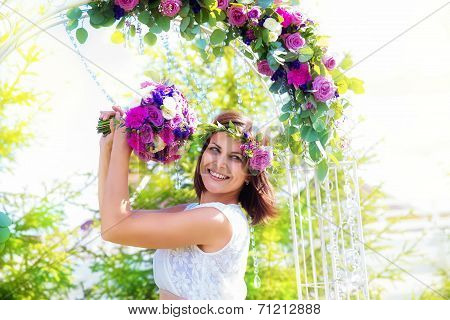 Bridesmaid With A Wedding Bouquet. Arch For Wedding Ceremony Decorated With Flowers In The Backgroun