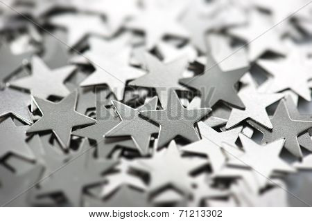 Silver stars. Silver metal stars scattered with reflective light.