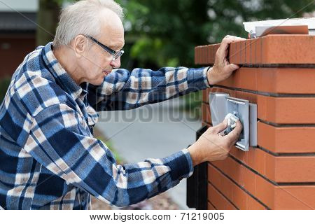 Man Repairing Intercom At The Gate