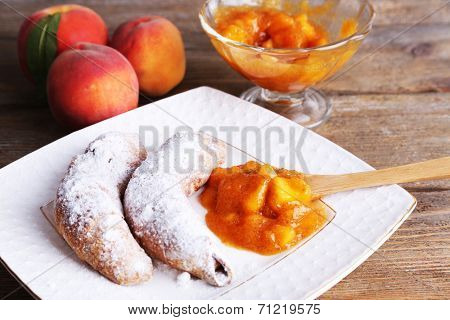 tasty peach jam with fresh peaches and croissants on wooden table