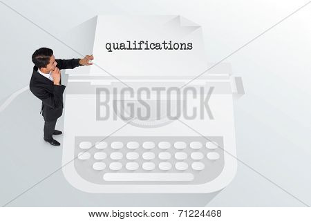 The word qualifications and thoughtful asian businessman pointing against typewriter