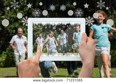 Hand holding tablet pc against happy multi generation family racing towards camera