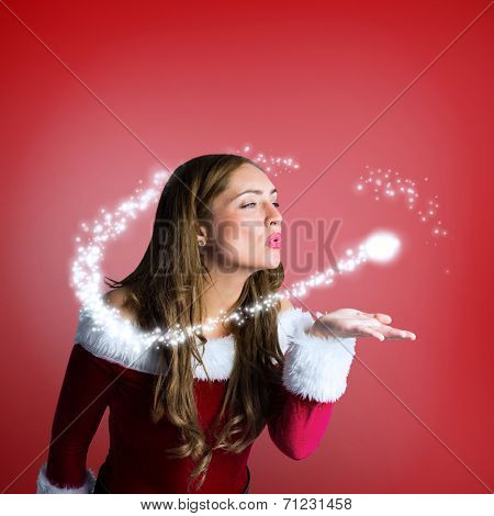 Sexy santa girl blowing a kiss against red vignette