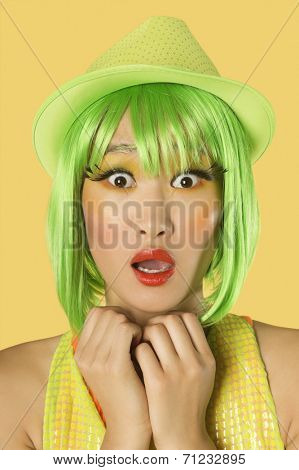 Portrait of shocked young woman with green hair against yellow background