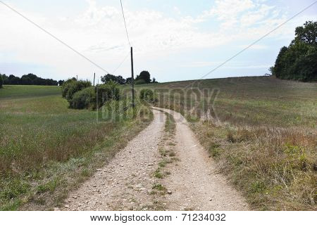 Unpaved road in grassy field against cloudy sky