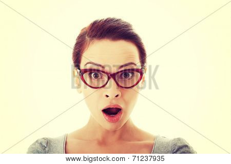 Young casual woman in eyeglasses expresses shock. Isolated on white.