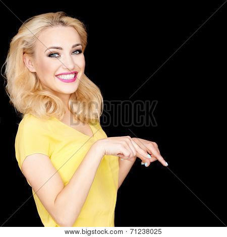 Beautiful blond woman on a black background standing sideways pointing downwards and looking at the camera with a playful grin