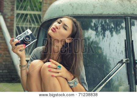 Urban girl has fun with vintage photo cameras outdoor near retro car, image toned.