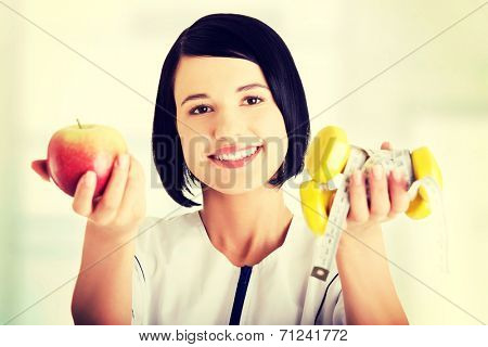 Woman dietician holding apple and dumbbells with measuring tape