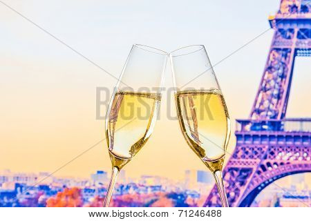 A Pair Of Champagne Flutes With Golden Bubbles On Blur Tower Eiffel Background
