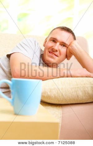 Man Relaxing On Sofa With Cup