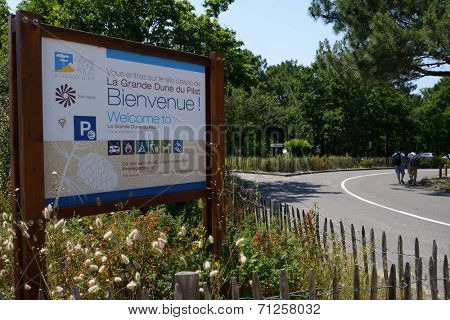 PILAT, FRANCE - JUNE 27, 2013: Welcome board and tourist going to the dune of Pilat. This dune is the biggest one in Europe, and it still grows