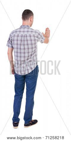 back view of man. Young man jeans presses down on something. Isolated over white background. Rear view people collection. backside view of person. she holds his hand open, palm forward