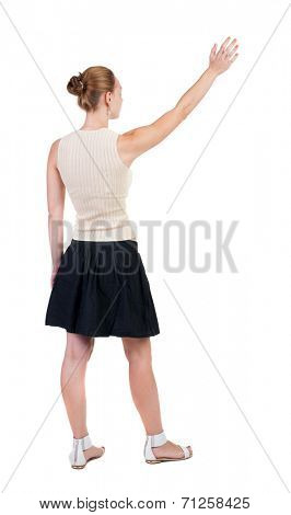 Back view of beautiful woman welcomes. Young teenager girl in dress hand waving from. Rear view  people collection.  backside view of person.  Isolated over white background.