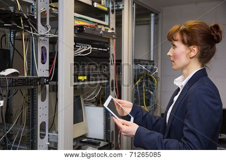 Pretty technician using tablet pc while looking at server in large data center