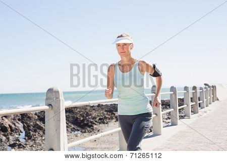 Fit mature woman jogging on the pier on a sunny day