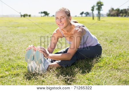 Fit mature woman warming up on the grass on a sunny day