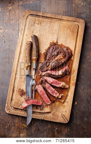 Medium Rare Grilled Beef Steak Ribeye With Knife And Fork For Meat On Cutting Board On Dark Wooden B