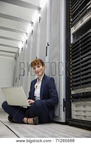 Technician sitting on floor beside server tower using laptop in large data center