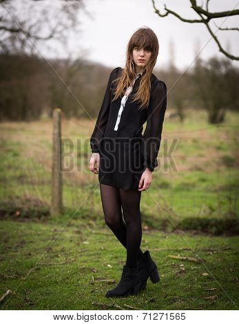 Beautiful Young Woman Dressed In Black In A Field
