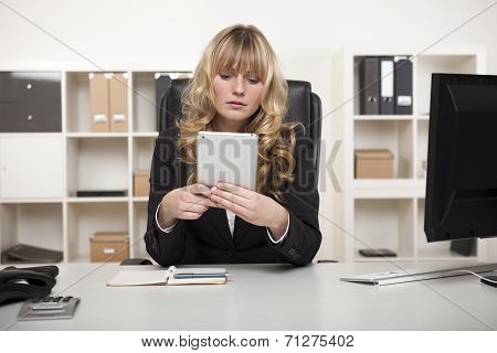 Young Woman Reading A Tablet In The Office