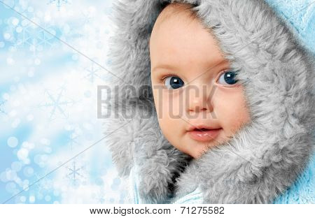 Beautiful baby girl on a snow flake background wearing a winter fur coat.