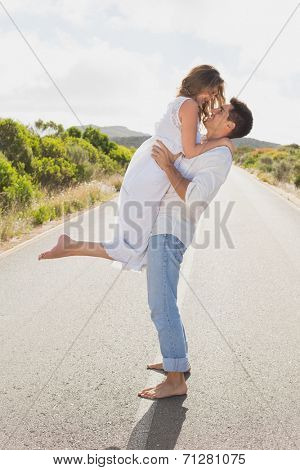 Side view of a young man carrying woman on countryside road