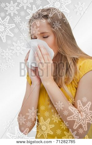 Close up of a blond woman blowing against snowflakes on silver