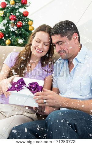 Loving couple opening Christmas gift against snow falling