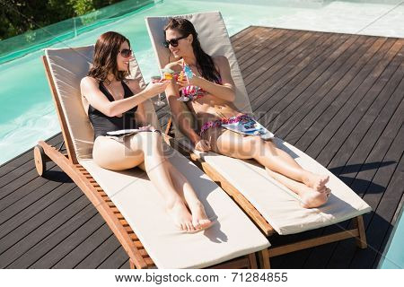 Two beautiful young women toasting drinks by swimming pool