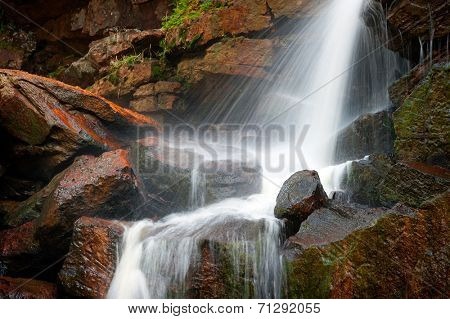 Wet rocks and splashes of water on mountain river waterfall