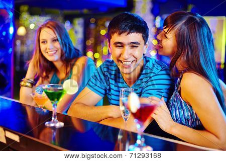 Portrait of pretty girl flirting with guy at party in the bar