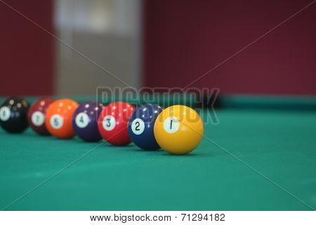 Yellow Snooker Ball With Number One On It With Other Colorful Balls Placed In A Row On A Table