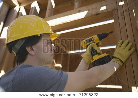 Young male architect drilling on a wooden beam at construction site