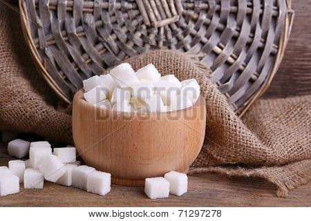 Refined sugar wooden bowl on table background